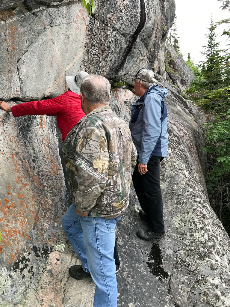 Chief Duncan Michano Jr., Band Manager JoAnne Michano, and Elder Cecil Twance investigating Biigtigong mzinaabkin'ganan (Biigtigong pictographs) in Biigtigong Nishnaabeg territory. (July 2018)